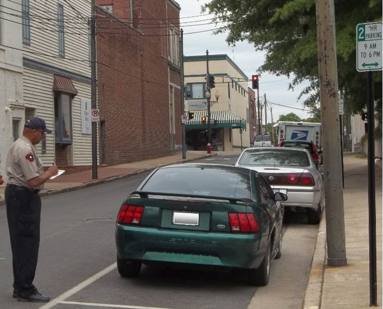 Parking Enforcement Officer Writing out a Ticket for Improperly Parked Mustang