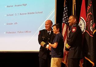 Aryana High receives graduation certificate from Police Chief Scott Booth, left, and Deputy Police C