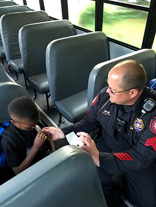 "Police officer rides bus as part of ""Badges on Buses"" program."