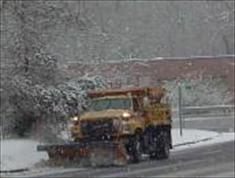 Orange truck plowing snow on street