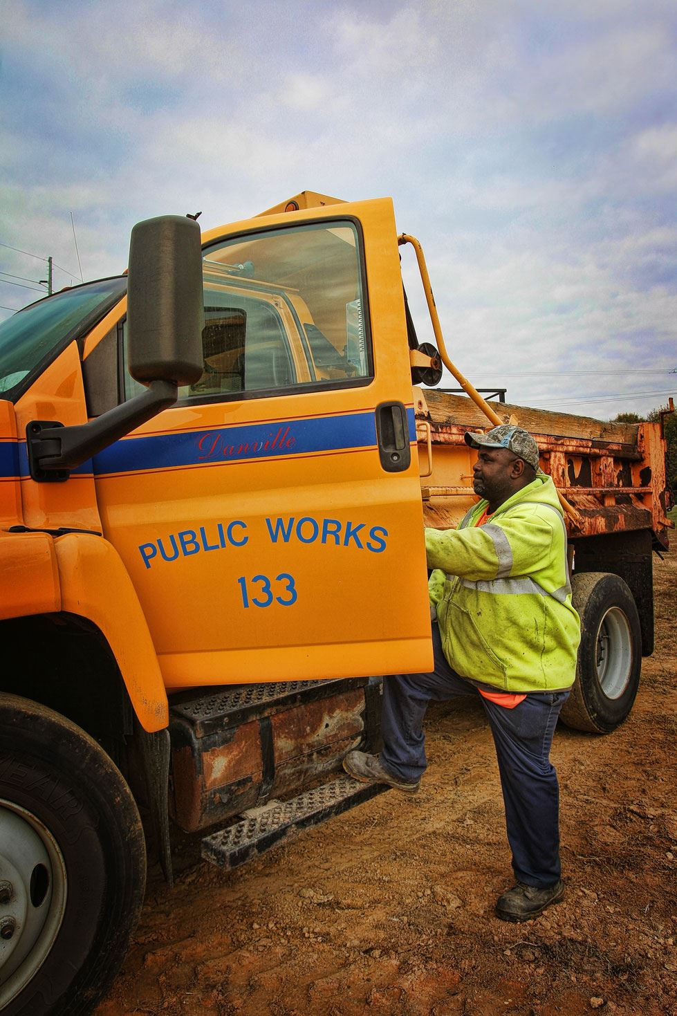 Man in yellow jacket climbing into oragne public works truck